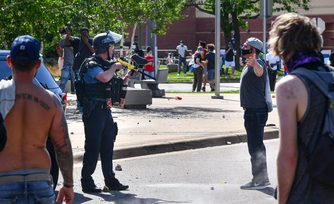 A St. Paul police officer armed with a non-lethal paintball-style weapon faces off with a protester in front of the Target store near the intersection of University Avenue West and Hamline Avenue North Thursday, May 28, 2020, in St. Paul, Minn.
