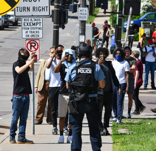 People record a police officer with their phones near the intersection of University Avenue West and Hamline Avenue North Thursday, May 28, 2020, in St. Paul, Minn.