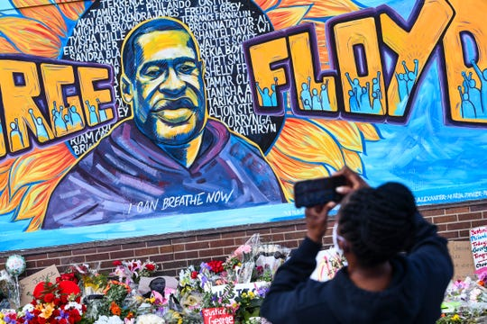 People take photographs of a mural in memory of George Floyd on a wall of the Cup Foods store Friday, May 29, 2020, at the corner of Chicago Avenue and East 38th Street in Minneapolis, Minn.
