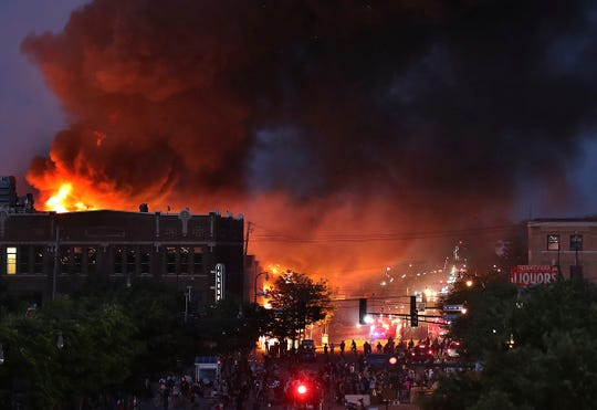 Seen from Hiawatha Avenue, a large fire burns Thursday, May 28, 2020, in Minneapolis during a third night of unrest following the death of George Floyd while in Minneapolis police custody Monday. (David Joles/Star Tribune via AP)