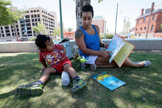 Raquel Mertz reads to Matthew Santacruz, 2, as Reopen Texas and Free to Play held a peacefull rally at Cleveland Square Park May 29 to urge the city to open parks and libraries.