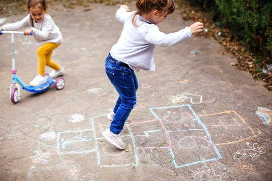 Little girls play hopscotch