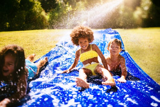 Children play on a slip and slide in a yard