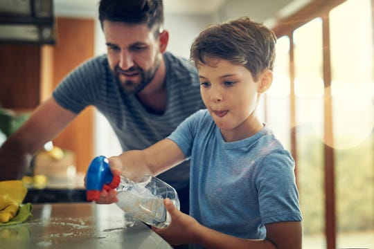 A father and son clean the kitchen counter together at home.