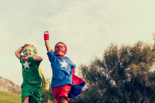 Children dressed as superheroes play outside.