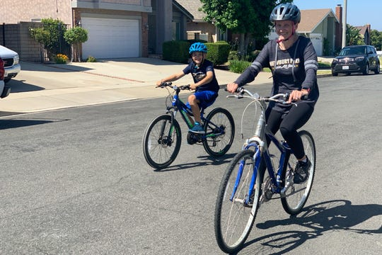 Kristina Lopez rides her 18-year-old Giant mountain bike with her 11-year-old son Joey near their home in Newbury Park.