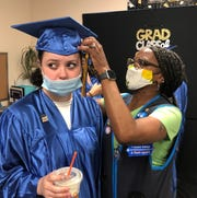 Vineland Walmart associate Dee Jenkins helps coworker Joslyn Yator of Vineland High School get ready for the Walmart commencement ceremony that honored employees earning high school diplomas or college degrees. May29, 2020