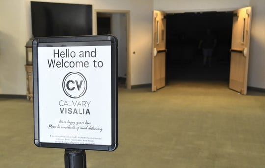"""A sign in the foyer welcomes congregants to Calvary Chapel of Visalia while asking them to """"be considerate of social distancing."""" The church resumed in-person services two weeks ago while still streaming online."""