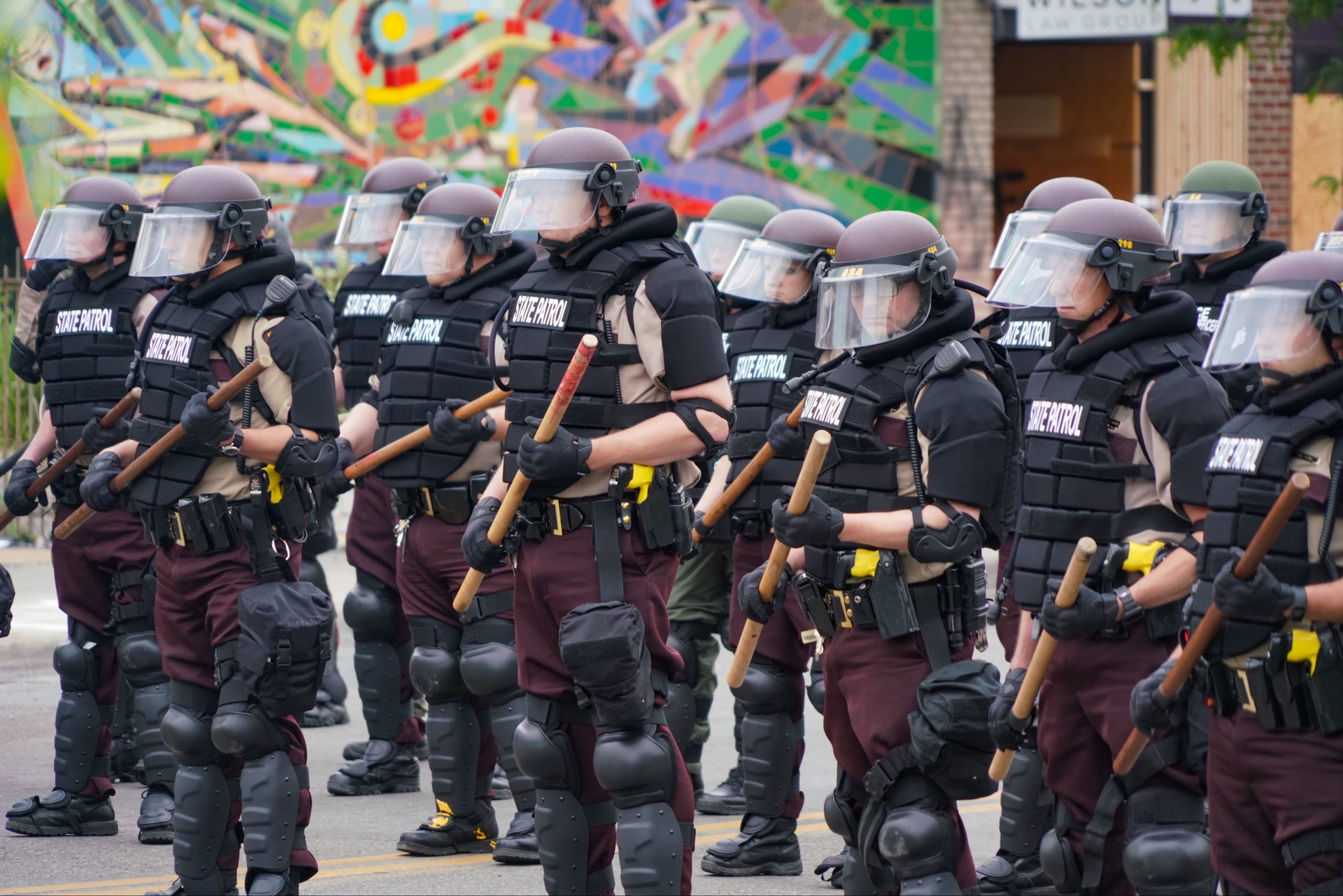 Armored members of the Minneapolis State Patrol stand guard in an intersection in front of burned out buildings in the Third Precinct of Minneapolis on Friday, May 29, 2020. The area was rocked by looting and widespread destruction overnight by protesters and rioters following peaceful gatherings for most of the day. Protesters were demanding justice for the death of George Floyd, who died after a white police officer knelt on his neck.