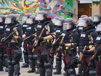 Armored members of the Minneapolis State Patrol stand guard in an intersection in front of burned out buildings in the Third Precinct of Minneapolis on Friday. The area was rocked by looting and widespread destruction overnight by protesters and rioters following peaceful gatherings for most of the day. Protesters were demanding justice for the death of George Floyd, who died after a white police officer knelt on his neck. Friday, May 29, 2020