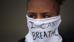 """A person wears a mask that reads """"I CAN'T BREATHE"""" as demonstrators continue to protest the death of George Floyd on May 29, 2020 in Minneapolis, Minnesota."""