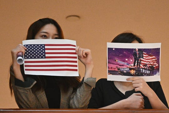 Two women hold up posters of the U.S. flag and a depiction of President Donald Trump, right, during a pro-democracy rally in a shopping mall in Hong Kong on May 28, 2020.