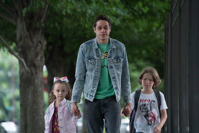 "Scott (Pete Davidson, center) walks Kelly (Alexis Rae Forlenza) and Harold (Luke David Blumm) to school in ""The King of Staten Island."""