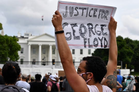 Protesters hold signs as they gather outside the White House in Washington, DC, on May 29, 2020 in a demonstration over the death of George Floyd, a black man who died after a white policeman kneeled on his neck for several minutes. -
