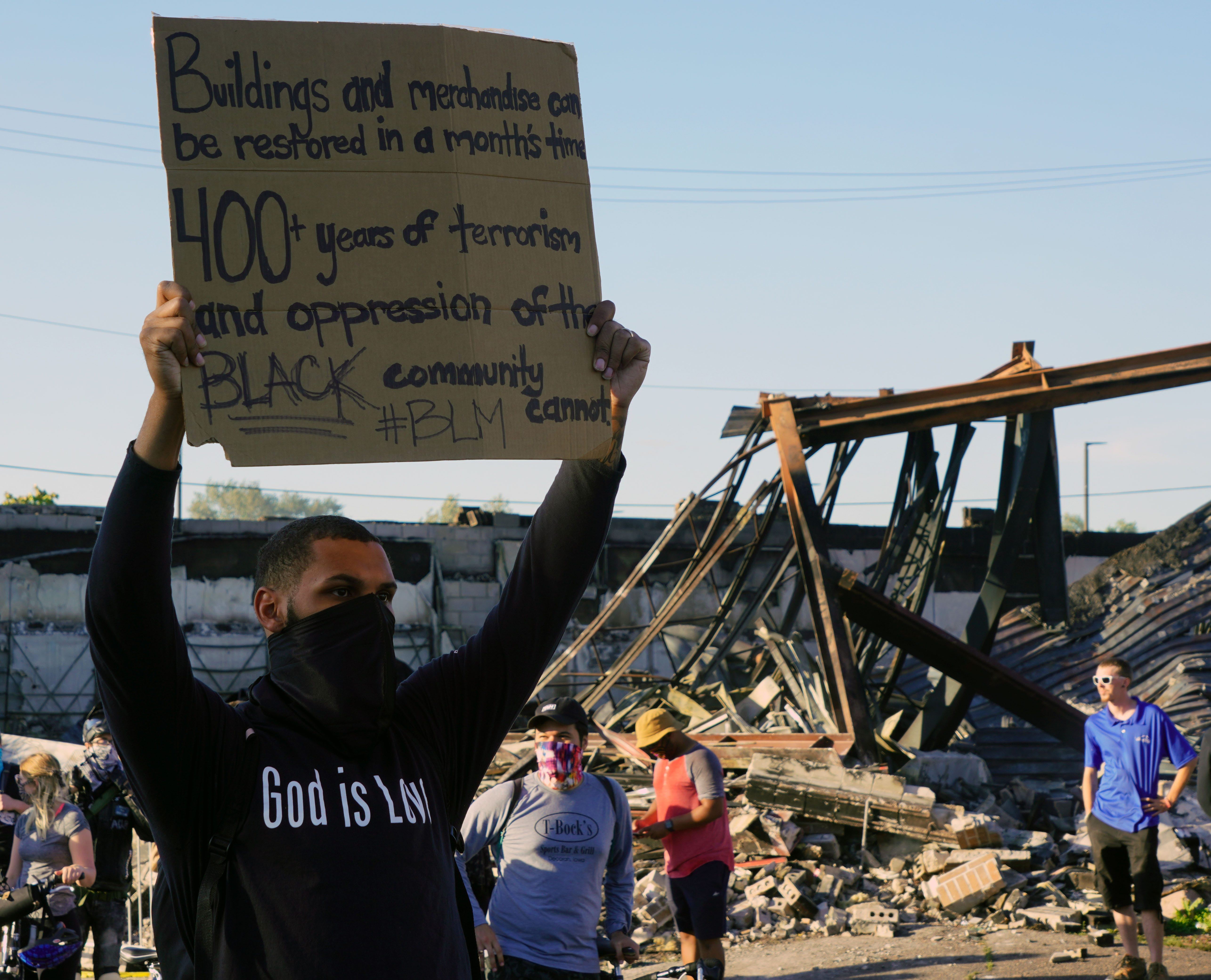 A protester holding a sign in front of a burned-out building Minneapolis during protests over the death of George Floyd on May 28, 2020.