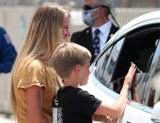Sitting in a Tesla vehicle, NASA astronaut Doug Hurley says goodbye to his wife, Karen Nyberg, and son, Jack, after he and a fellow astronaut walked out of the Operations and Checkout Building. They were on their way to the SpaceX Falcon 9 rocket with the Crew Dragon spacecraft on launch pad 39A at the Kennedy Space Center on May 30, 2020, in Cape Canaveral, Florida. The inaugural flight will be the first manned mission since the end of the space shuttle program in 2011 to be launched into space from the United States.