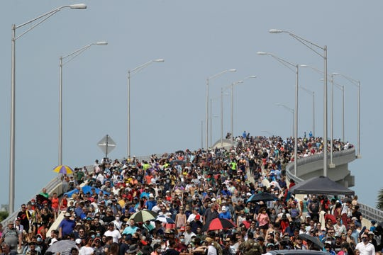 Spectators walk from their vantage point on a bridge in Titusville, Fla. after watching SpaceX Falcon 9 lift off with NASA astronauts Doug Hurley and Bob Behnken in the Dragon crew capsule, Saturday, May 30, 2020 from the Kennedy Space Center at Cape Canaveral, Fla. The two astronauts are on the SpaceX test flight to the International Space Station. For the first time in nearly a decade, astronauts blasted towards orbit aboard an American rocket from American soil, a first for a private company.