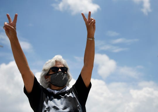 Nelda Martinez holds up peace signs during the Stand in Solidarity event for George Floyd, Saturday, May 30, 2020, in downtown Corpus Christi. About a 100 people were protesting the death of George Floyd and the use of excessive force by police.