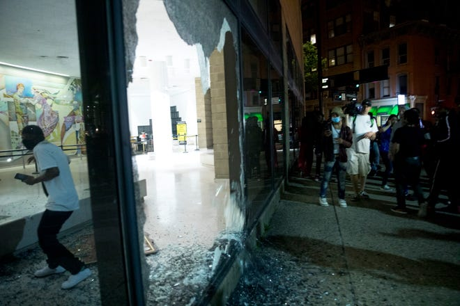 A protestor jumps through a broken window at the Hamilton County Justice Center in Cincinnati on Friday night. The protest started in response to the death of George Floyd.