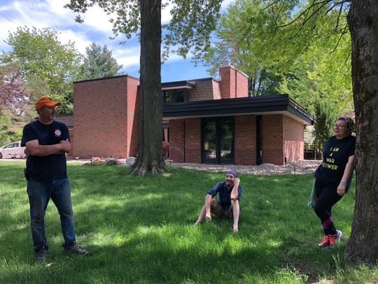 Charles Mikkelsen, left, his son Stewart Mikkelson and wife, Linda Mikkelsen take a break from cleaning up their 1966 midcentury modern home in Midland, Michigan, on Wednesday, May 27, 2020.