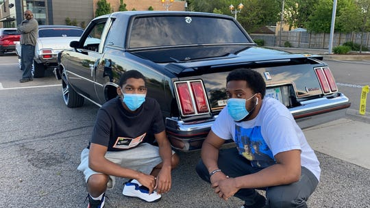 Jaylon Carr (left) and Elijah Hood of Pontiac wore masks as they enjoyed the classics with Carr's 1979 Oldsmobile Cutlass Supreme on Woodward Avenue. In the background, Carlos Carr, also masked, with his '71 Olds Cutlass.