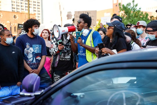 A group of protesters try to stop another group of protesters from vandalizing a police vehicle outside of the Detroit Police headquarters in Detroit on Friday, May 29, 2020.