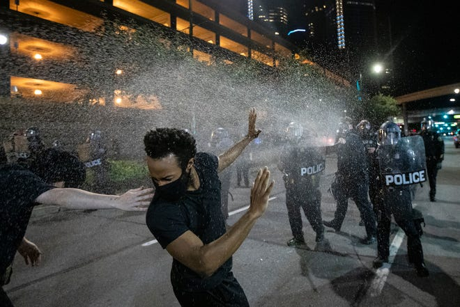 Protesters are sprayed with pepper spray by Detroit police officers in riot gear in downtown after an afternoon march and rally against police brutality extended into the evening and became contentious on Friday, May 29, 2020 in Detroit.