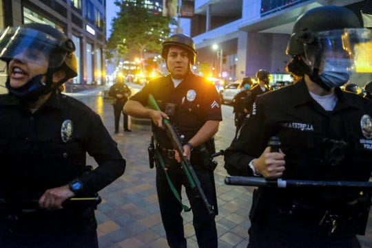 Police officers move forward to clear the street during a protest over the death of George Floyd, Friday in Los Angeles.