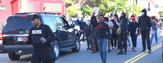 A protester yells at Detroit Police Special Response Team members as they back onto Trumbull.