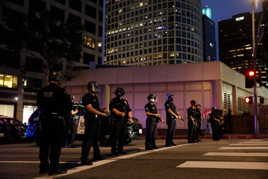 Police officers stand guard during a protest over the death of George Floyd, Friday, May 29, 2020, in Los Angeles.