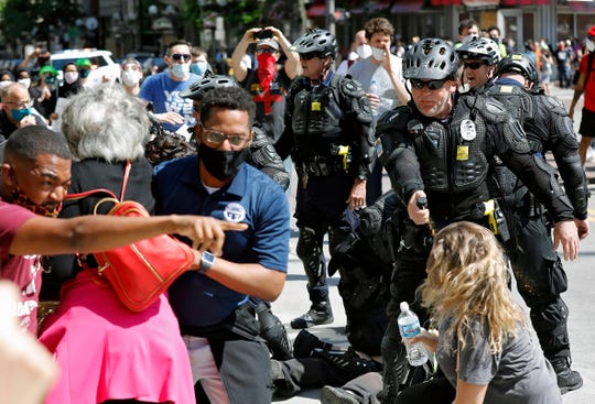Congresswomen Joyce Beatty and Columbus City Council President Shannon Hardin try to intervene as Columbus Police use pepper spray on protesters during a protest on the death of George Floyd on South High Street near the Ohio Statehouse in Columbus, Ohio on Saturday.