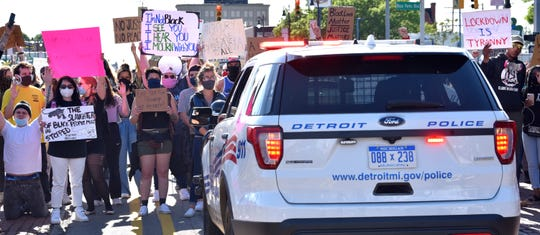 As Detroit police officers escort protesters on Michigan Avenue westbound, protesters turn and confront officers at Rosa Parks Blvd.