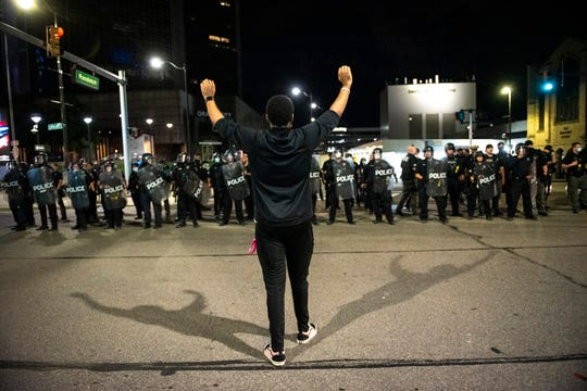 A protester holds his hands up while facing police officers during a demonstration against police brutality in Detroit on Friday, May 30, 2020.