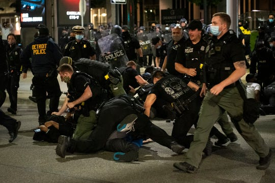 Police officers tackle protesters during a demonstration against police brutality in Detroit on Friday, May 30, 2020.