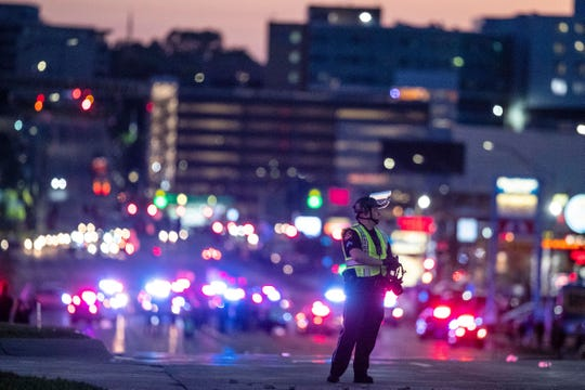 An Omaha police officer holds his gas mask on Dodge Street just west of 72nd Street, Friday, May 29, 2020, during a protest in Omaha, Neb.