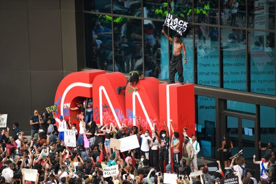 Demonstrators paint on the CNN logo during a protest, Friday, May 29, 2020, in Atlanta, in response to the death of George Floyd in police custody on Memorial Day in Minneapolis.