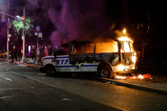 A Police vehicle burns after protesters rallied at Barclays Center over the death of George Floyd, a black man who died Memorial Day while in Minneapolis police custody, Friday, May 29, 2020, in the Brooklyn borough of New York.