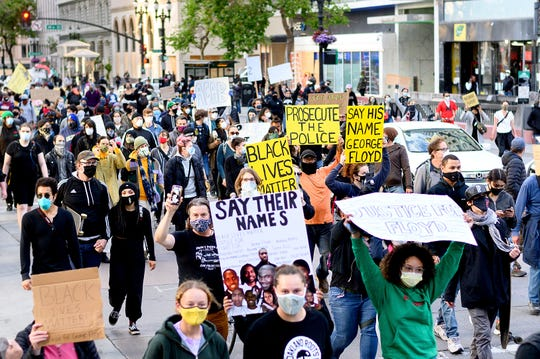 Demonstrators march in Oakland, Calif., on Friday, May 29, 2020, to protest the Monday death of George Floyd, who died in police custody while handcuffed in Minneapolis.