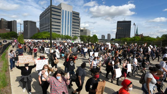 Protesters march on Michigan Avenue in front of Detroit police headquarters