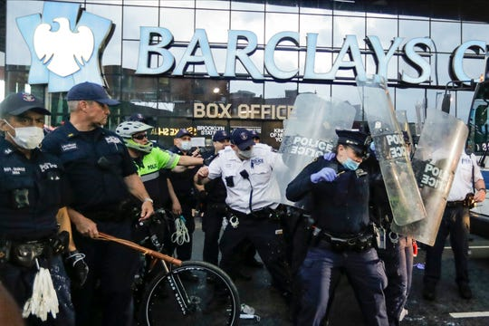 Police officers protect themselves with shields as protesters throw debris during a rally Friday in the Brooklyn borough of New York.