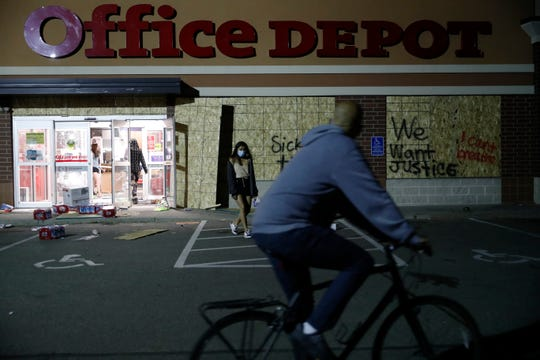 People walk inside and in the parking lot of an Office Depot store, Friday, May 29, 2020, in Minneapolis.