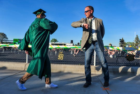 CMR Principal Kerry Parsons, in a break from tradition due to the coronavirus, gives out elbow bumps instead of handshakes and hugs, and was also unable to turn the tassels for the Class of 2020 graduates during Friday evening's graduation ceremony at Montana ExpoPark.