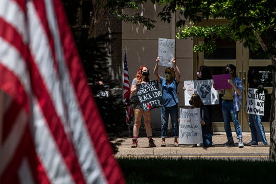 "Shiloh Parish, left, holds up sign to protest against the police violence toward African Americans in America. A peaceful protest in front of Jackson City Hall occurred Saturday, May 30, 2020 in the afternoon. The protestors helds signs reading ""Black Lives Matter"" and ""I can't breathe"" after George Floyd's death May 25 in Minneapolis."