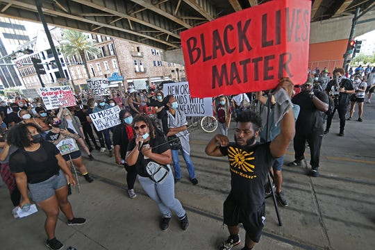 Protestors stop on Canal Street under the I-10 for speeches as thousands of people march from City Hall to New Orleans Police headquarters to protest the killing by police of George Floyd and others on Saturday, May 30, 2020.