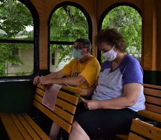 Greg Rice listens to the tour guide while Amy Rice checks the tour description during the Glass Town Trolley Tour Saturday, May 30. The tour started at the main branch of the Fairfield County District Library and visited numerous sites in Lancaster with historical meaning.