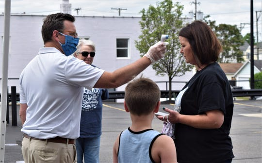 Jonathan Eyman, left, checks Amanda Woodrum's temperature before she and her family take the Glass Town Trolley Tour on Saturday, May 30. The tour started at the main branch of the Fairfield County District Library and visited numerous sites in Lancaster with historical meaning.