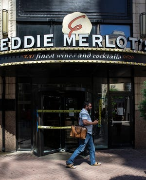 A man walks past the entrance of Eddie Merlot's Restaurant on Fourth Street, which was looted during a protest over the shooting of Breonna Taylor. May 30, 2020