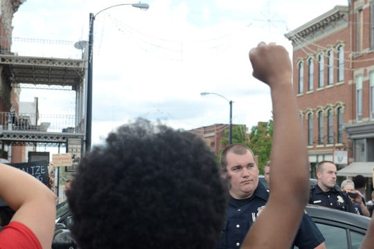 """A large group of protesters surrounded two police cars and officers that stood outside them, chanting """"hands up, don't shoot."""""""