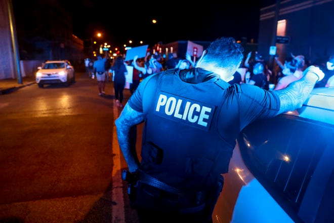 A Memphis Police Officer leans against their squad car while the line of protesters passes a corner at downtown in Memphis, Tenn., on Friday, May 29, 2020.