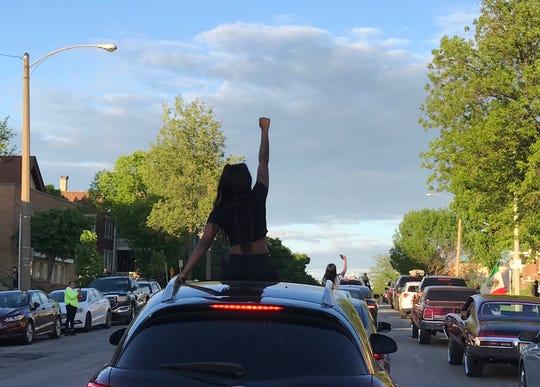 Eine Unterstützerin erhebt ihre Faust aus Solidarität mit Demonstranten, als eine Menge von mehreren hundert Autos und Fußgängern auf der National Avenue nach Osten fährt.